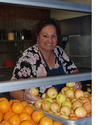 Photo of cafeteria worker serving fruit